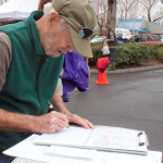 On the first day of the petition signing drive, loyal Farmers' Market customer, Lin Jensen, takes time from his shopping to sign the petition. Photo by Karen Laslo